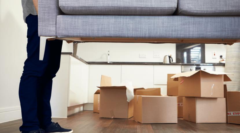 a boy lifting sofa in home shifting